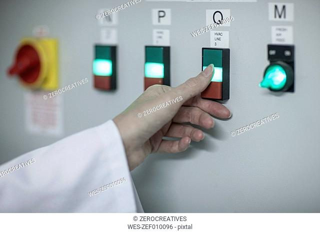 Close-up of woman switching on power switch in factory