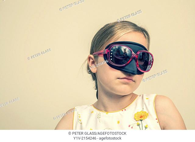 Preteen blond girl wearing a mask and sunglasses