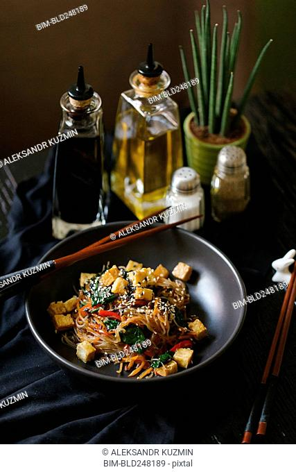 Chopsticks on the bowl with noodles and tofu
