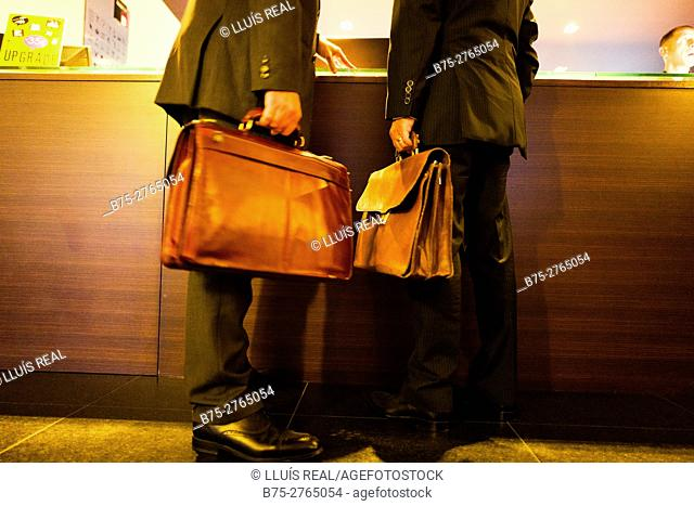 Two unrecognizable executives wearing suit and holding leather briefcases at Hotel reception. Porto, Portugal