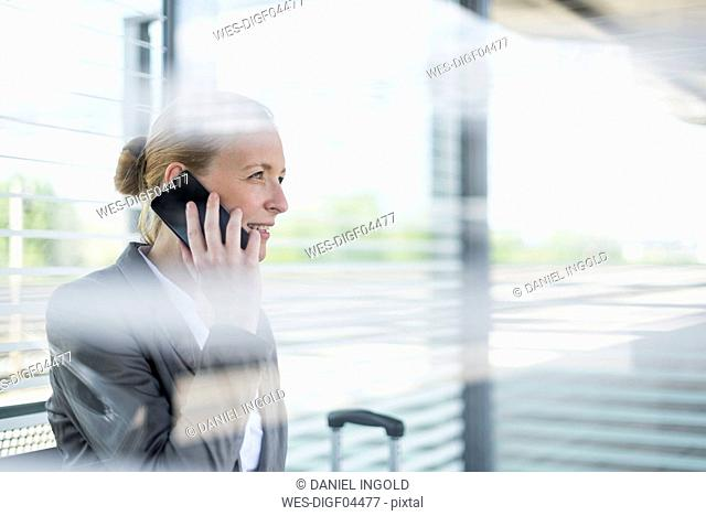Portrait of mature businesswoman on the phone waiting at platform