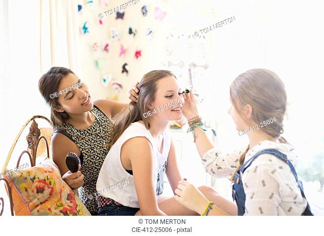 Three teenage girls doing make up and brushing hair in bedroom