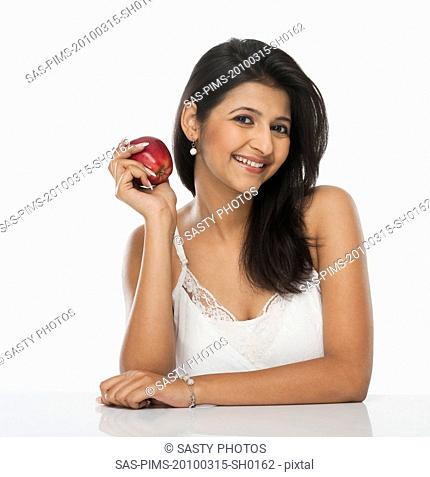 Woman holding an apple and smiling