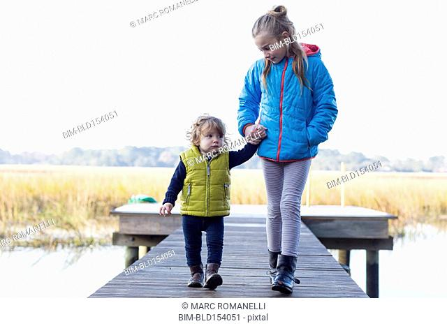 Caucasian brother and sister walking on wooden dock