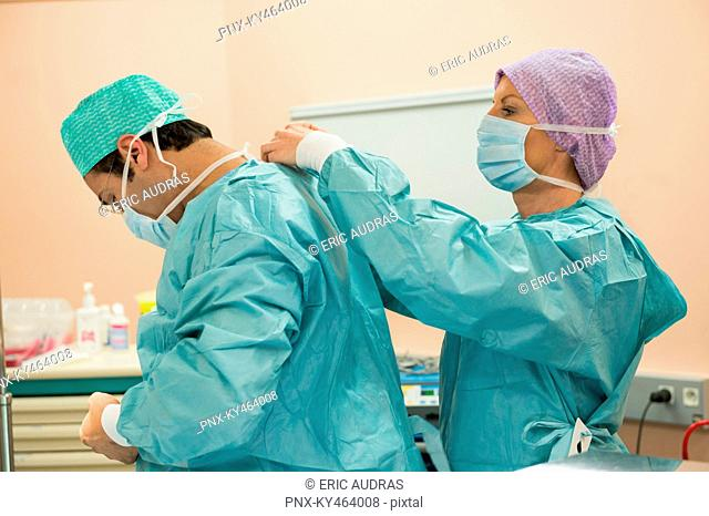 Female surgeon helping a male surgeon putting on protective clothe
