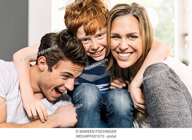 Portrait of happy young family sitting on their couch at living room