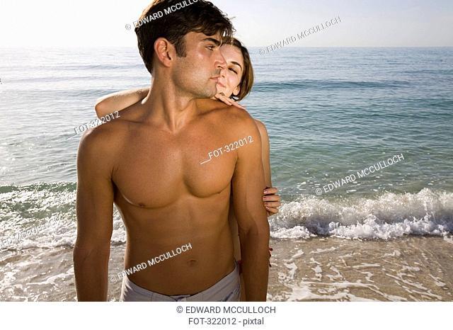 Woman standing behind man on beach
