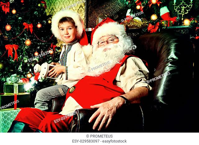 Santa Claus in his everyday clothes in Christmas home d?cor. Happy little boy helps Santa Claus get ready for Christmas
