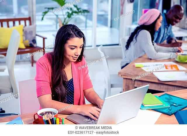 Businesswoman using laptop while working with colleagues