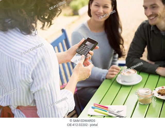Couple watching waitress using credit card reader at outdoor cafe