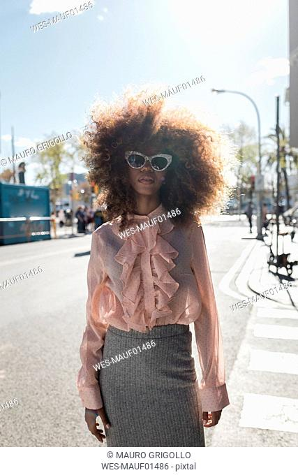 Portrait of beautiful young woman with afro hairdo in the city