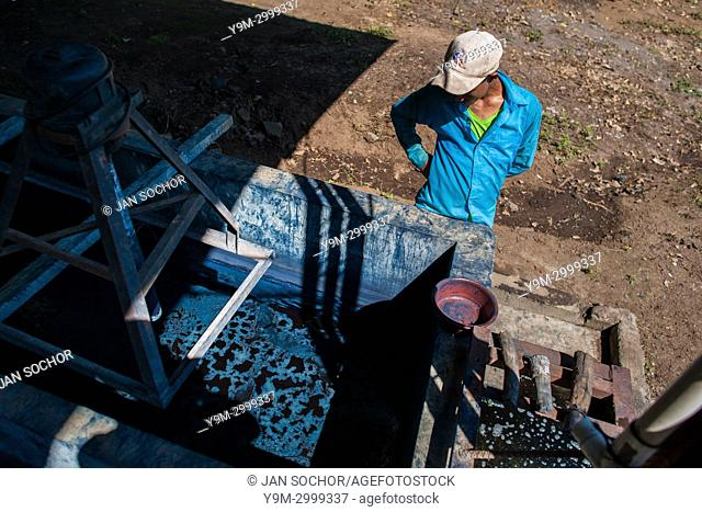 A Salvadoran farm worker controls the indigo processing while water solution is slowly siphoning out from a concrete tank at the semi-industrial manufacture...