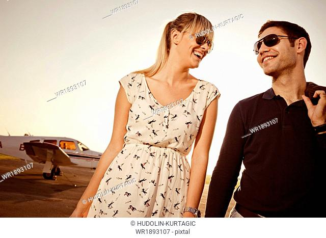 Couple with luggage in front of private airplane