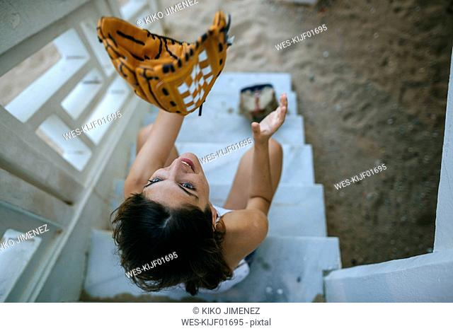 Young woman playing with baseball glove