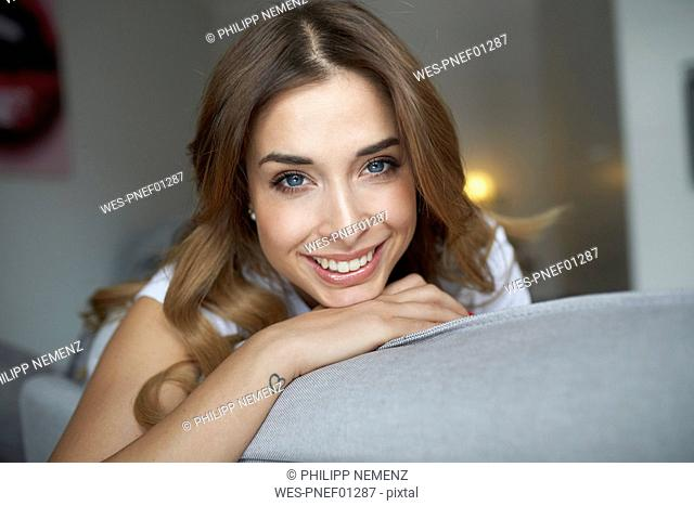 Portrait of smiling young woman on couch
