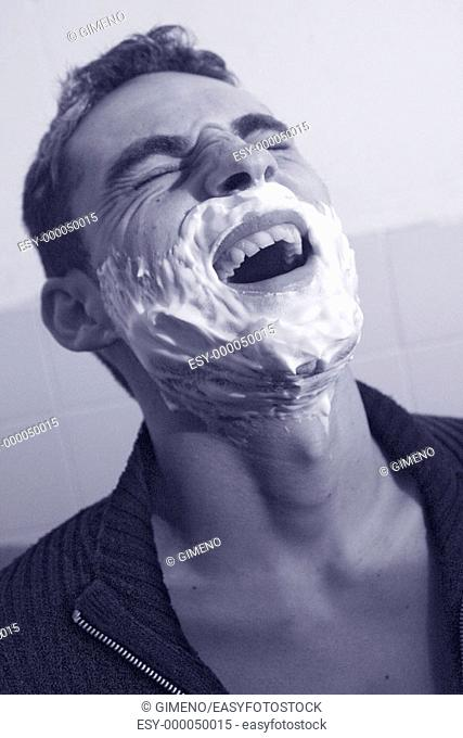 Young man with shaving cream on face screaming