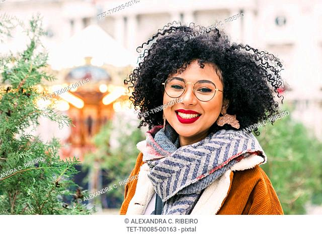 Portrait of smiling young woman wearing glasses and red lipstick