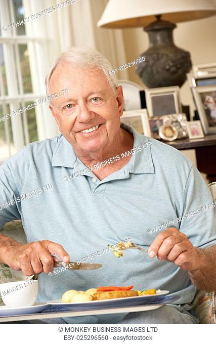 Senior Man Enjoying Meal At Home