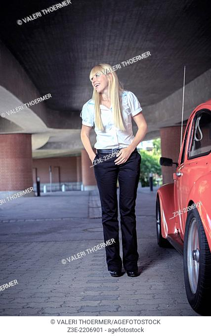 urban portrait of a young woman with a classic car