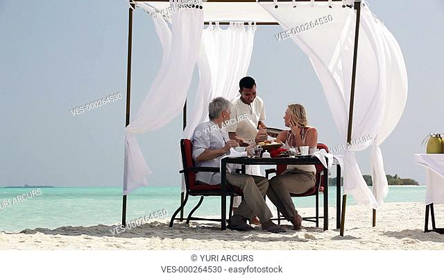 Friendly waiter serving breakfast to a happy mature couple sitting in a gazebo on a pristine beach