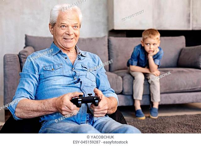I should not have taught him. Upset weary observant boy sitting on a couch and watching how his grandpa playing video games