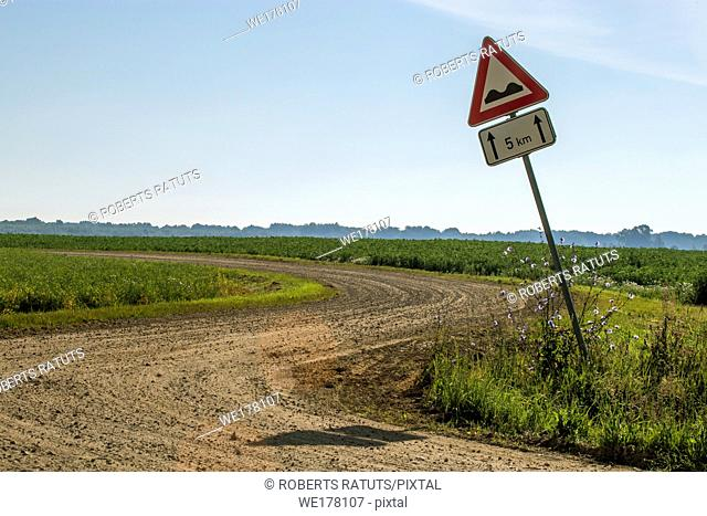 Road sign in countryside. Summer landscape with rural road, wood and cloudy blue sky. Classic rural landscape in Latvia. .