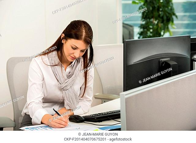 Businesswoman sitting while writing at computer desk