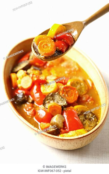 Vegetable stew in bowl with spoon, high angle view