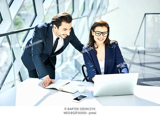 Smiling businesswoman and businessman using laptop at desk in modern office