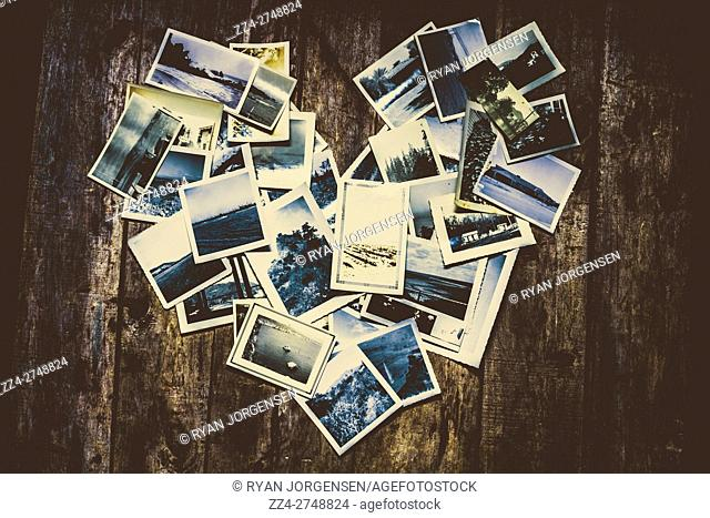 Above view of instant printed photos on wooden backdrop arranged in heart shape
