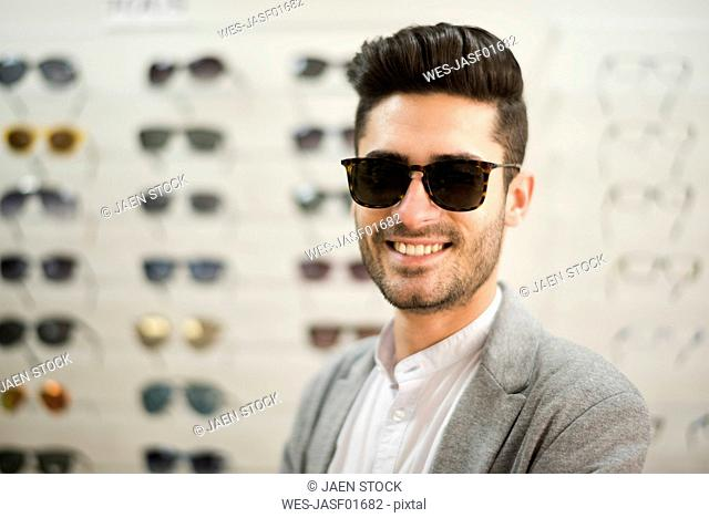 young man trying on glasses at the optician's
