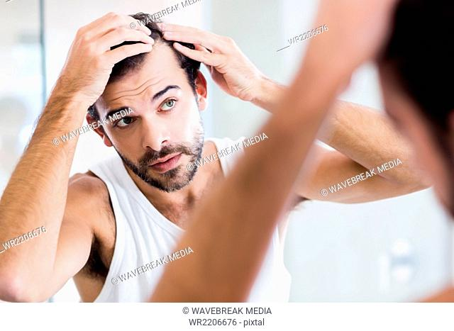 Concentrated man looking at his hair in mirror