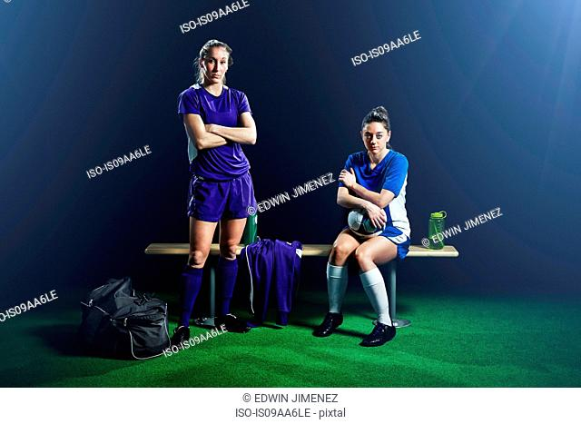 Portrait of two female soccer players on bench