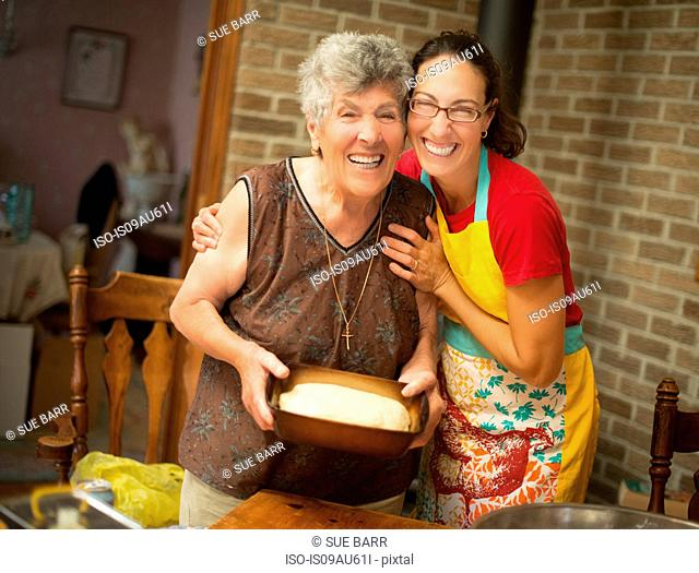Women at home preparing bread dough looking at camera smiling