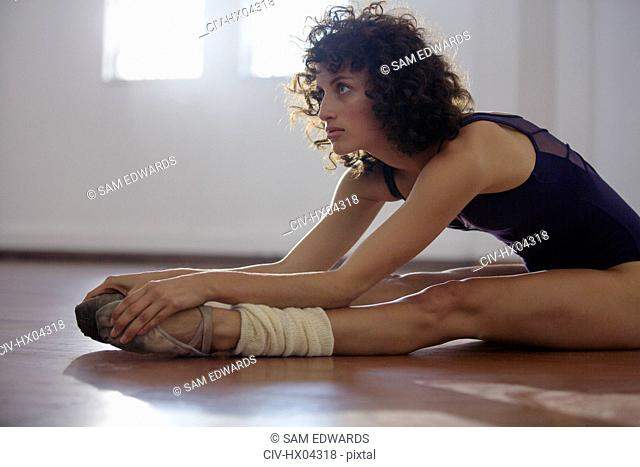 Focused young female dancer stretching legs in dance studio