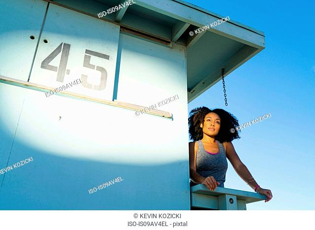 Mid adult woman standing on look out tower at beach, looking at view