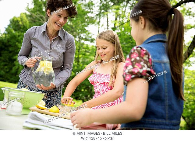 A summer family gathering at a farm. A woman and two children standing outside by a table, laying the table. Making lemonade