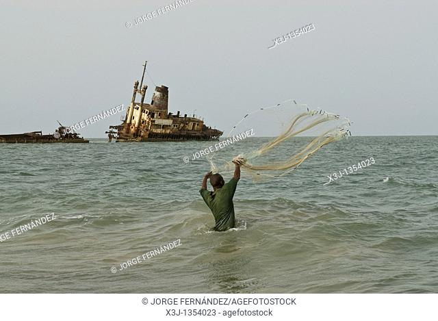 Man fishing with a net from the shore in front of a shipwreck, Palmarin, Senegal, Africa