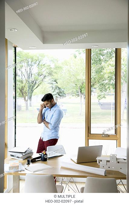Young man talking on cell phone working in dining room