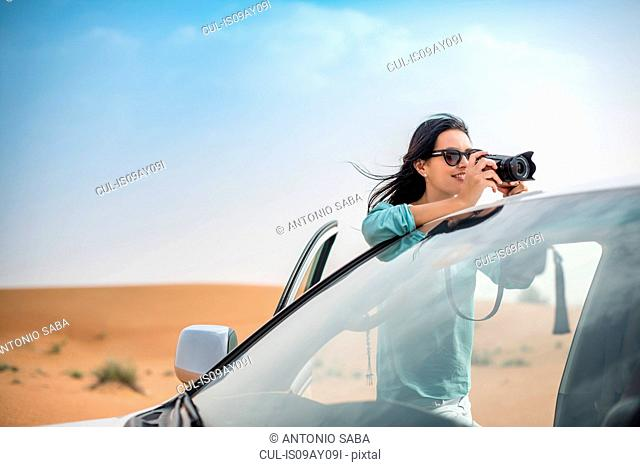 Female tourist photographing from off road vehicle in desert, Dubai, United Arab Emirates