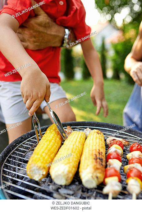 Boy turning a corn cob during a barbecue in garden