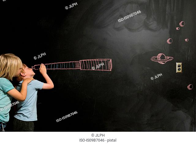 Boys looking through imaginary telescope drawn on blackboard