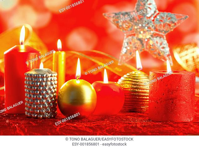 Christmas card candles red and golden in a row on blurred background