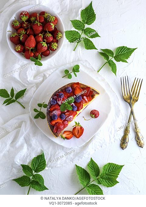 half a pie from cottage cheese and fresh strawberries, near two iron forks, white background, top view