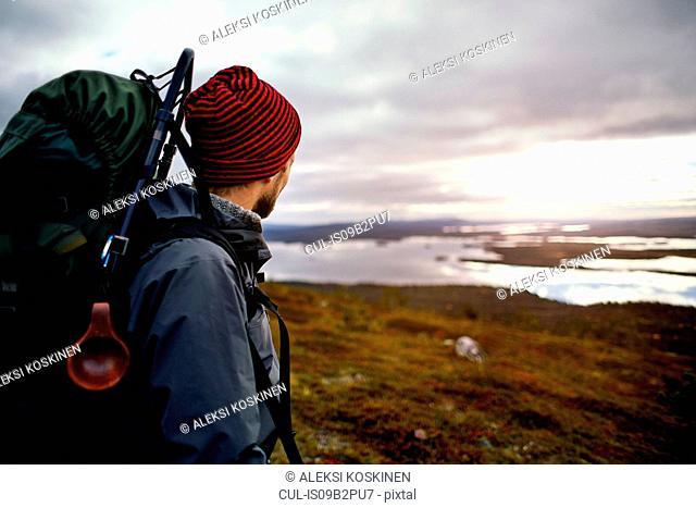 Hiker enjoying view of lake, Keimiotunturi, Lapland, Finland