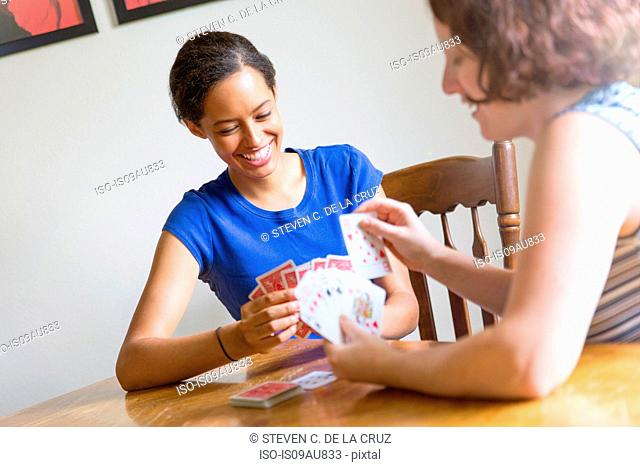 Angled view of young women sitting at dining table playing cards smiling