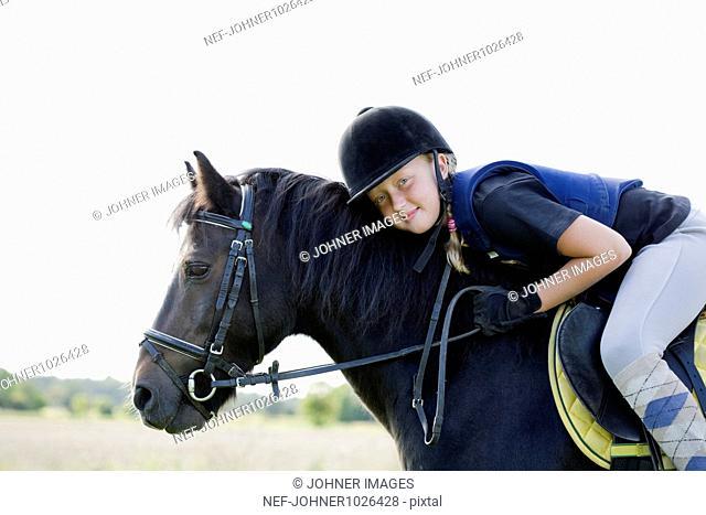 England, Cornwall, Dartmoor, portrait of girl (10-11) riding horse