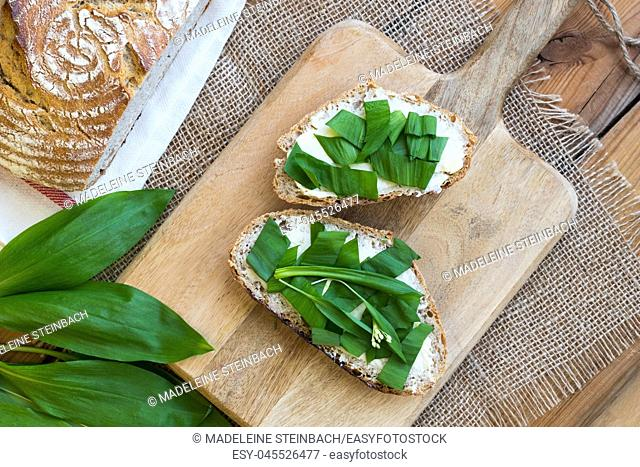 Slices of sourdough bread with butter and wild garlic, top view