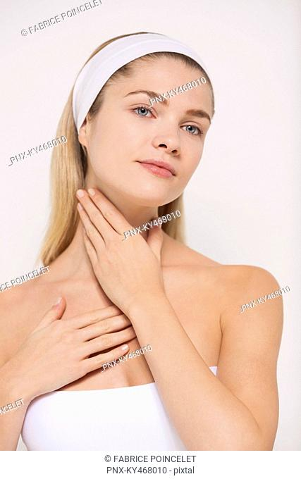 Beautiful woman applying moisturizer on her neck