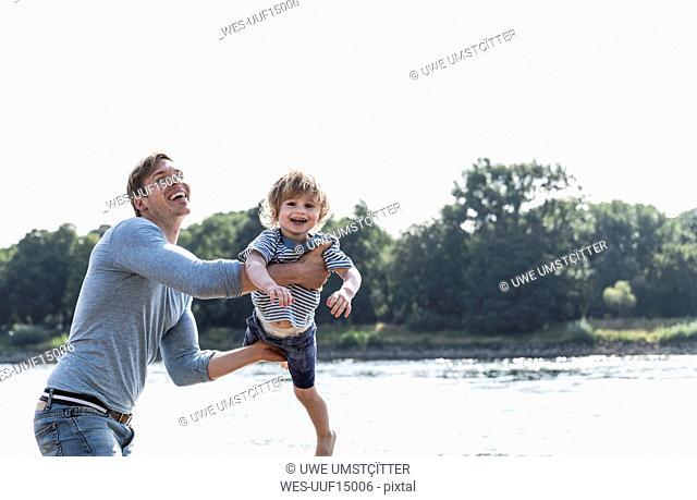 Father and son having fun at the riverside